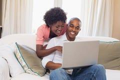 Gulliga par som kopplar av på soffan med bärbara datorn royaltyfria foton