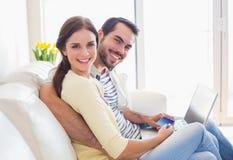 Gulliga par som kopplar av på soffan med bärbara datorn Arkivbilder