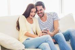 Gulliga par som kopplar av på soffan med smartphonen Royaltyfri Bild