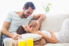 Gulliga par som kopplar av på soffan på frukosten Arkivbilder