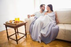 Gulliga par som kopplar av på soffan under filten Royaltyfria Bilder