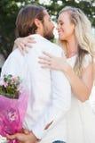 Gulliga par som kramar på ett datum Arkivfoto