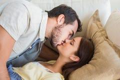 Gulliga par som kysser på soffan Royaltyfri Fotografi
