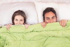Gulliga par som ligger i säng under räkningarna Royaltyfri Bild