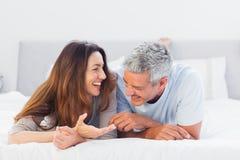 Gulliga par som ligger på säng som tillsammans talar Arkivbild