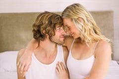 Gulliga par som omfamnar huvudet - - head i sängen Royaltyfri Foto