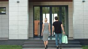 Gulliga par som skriver in det lyxiga huset med shoppingpåsar arkivfilmer
