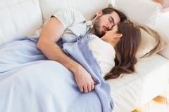 Gulliga par som ta sig en tupplur på soffan Arkivbild