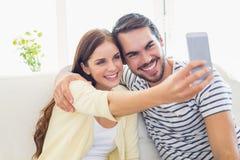 Gulliga par som tar en selfie på soffan Arkivfoto