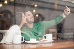 Gulliga par som tar selfie i en coffee shop arkivfoton