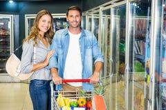 Gulliga par som tillsammans gör livsmedelsbutikshopping Arkivbilder