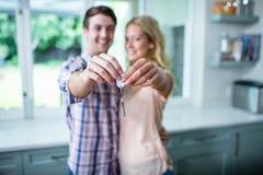 Gulliga par som visar deras nya hem- tangenter Royaltyfri Foto