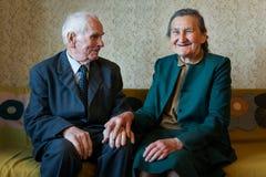 Gulliga 80 plus det åriga gifta paret som poserar för en stående i deras hus Förälskelseför evigtbegrepp Arkivfoto