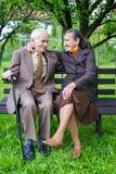 Gulliga 80 plus det åriga gifta paret som poserar för en stående i deras trädgård Förälskelseför evigtbegrepp Royaltyfri Foto
