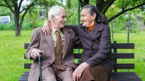 Gulliga 80 plus det åriga gifta paret som poserar för en stående i deras trädgård Förälskelseför evigtbegrepp Arkivbild