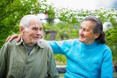 Gulliga 80 plus det åriga gifta paret som poserar för en stående i deras trädgård Förälskelseför evigtbegrepp Fotografering för Bildbyråer