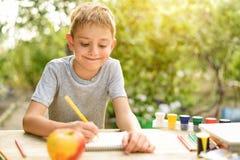 Gulliga pojkeattraktioner med blyertspennastilleben ?ppen luft Tr?dg?rd i bakgrunden id?rikt begrepp royaltyfria foton