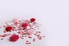 Gulliga röda spridda paljetthjärtor med tyg blommar på en vit bakgrund Arkivfoto