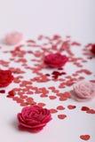 Gulliga röda spridda paljetthjärtor med tyg blommar på en vit bakgrund Fotografering för Bildbyråer