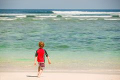 Gulliga 7 år gammal pojke i röd mest rushwest baddräkt på den tropiska stranden med det vita sand- och gräsplanhavet Arkivfoto