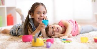 Gulliga roliga barn som hemma spelar med dishwareleksaker arkivbilder