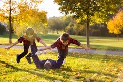 Gulliga roliga barn som spelar med deras fader i parkera, autu Arkivbilder