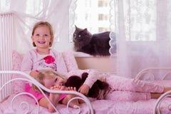 Gulliga roliga små flickor (systrar) spelar i säng, på fönstret sitter Arkivfoto