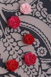 Gulliga rosa färger och röda blommor på en mönstrad bakgrund Royaltyfria Bilder