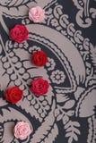 Gulliga rosa färger och röda blommor på en mönstrad bakgrund Arkivfoto
