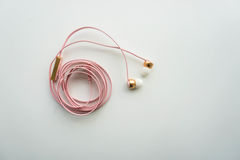 Gulliga rosa hörlurar för smartphone Fotografering för Bildbyråer