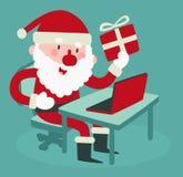 Gulliga Santa Holding en gåva på datoren Royaltyfri Bild