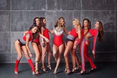 Gulliga sju gå-går sexiga flickor i röd tävlings- dräkt Arkivbilder
