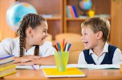 Gulliga skolbarn som har gyckel i klassrum royaltyfria foton