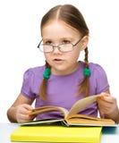 Gulliga slitage exponeringsglas för liten flickaavläsningsbok arkivfoton