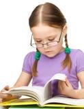 Gulliga slitage exponeringsglas för liten flickaavläsningsbok royaltyfria bilder