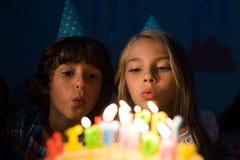 gulliga små barn på partihattar som blåser stearinljus arkivbilder