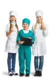Gulliga små barn som kläs som att se för doktor Arkivfoton