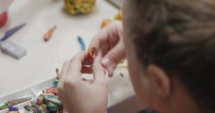 Gulliga små barn som sitter på skrivbordet, hugger olika diagram från gjort av kulör modellera plastellina i arkivfilmer