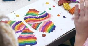 Gulliga små barn som sitter på skrivbordet, hugger olika diagram från gjort av kulör modellera plastellina i lager videofilmer