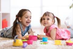 Gulliga små barn som spelar med kitchenware, medan ligga på golv hemma arkivbild