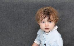 Gulliga små behandla som ett barn att posera, sammanträde och att se kameran Royaltyfri Bild