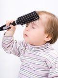 Gulliga små behandla som ett barn att spela med en hårborste royaltyfri foto