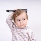 Gulliga små behandla som ett barn att spela med en hårborste arkivbilder