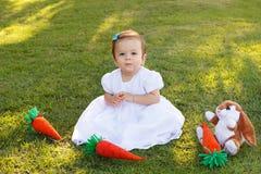Gulliga små behandla som ett barn flickan i den vita klänningen med den leksakkanin och moroten Arkivbilder