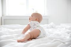 Gulliga små behandla som ett barn krypning på säng Arkivbild