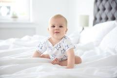 Gulliga små behandla som ett barn krypning på säng Royaltyfria Bilder