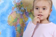 Gulliga små behandla som ett barn med den drömlika framsidan på världskartabakgrund arkivfoto