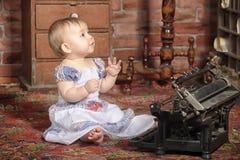 Gulliga små behandla som ett barn med den retro stilskrivmaskinen Arkivfoton