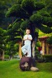 Gulliga små behandla som ett barn pojken, att meditera för unge som står på stenen nära bonsaiträdet Royaltyfri Bild