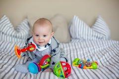 Gulliga små behandla som ett barn pojken som hemma spelar i säng med massor av colorf Royaltyfria Bilder